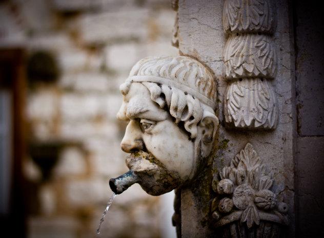 Gebeeldhouwd hoofd bij waterbron in Frankrijk