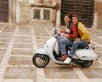 Vrouw en man op scooter in Italie